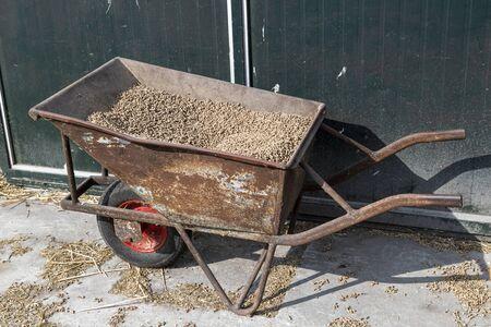 Old rusty wheelbarrow with chunks feed on a dairy farm in the Netherlands
