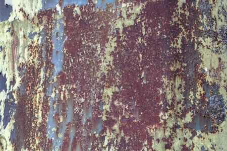 Peeling rusty metal round silo into a beautiful color as a full-screen background picture