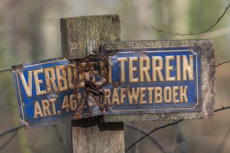 Old weathered sign forbidden entry in Dutch language on a pole
