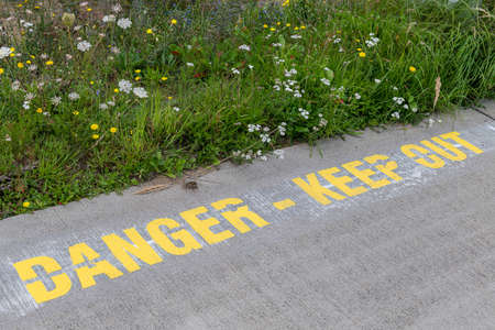Text Danger Keep Out nearby a beautiful green strip of plants at an airport