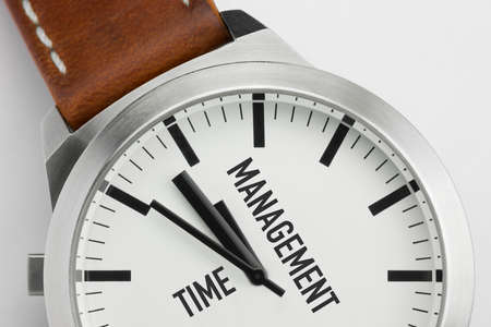 Macro photo of a modern metal watch with Time Management text on the dial