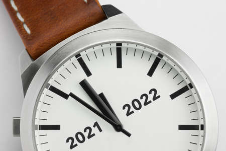 Macro photo of a modern metal watch with the text Two thousand and twenty one and two thousand and twenty two on the dial Zdjęcie Seryjne