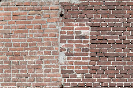 Facing bricks in a repaired wall in a dark red color in chain bond to an old building in the Netherlands