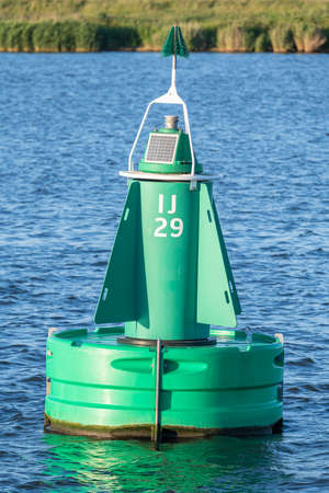 Green modern shipping buoy on the river IJ in Amsterdam in the Netherlands