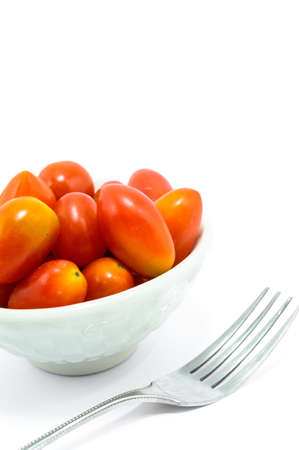 Cherry tomato in a bowl with fork, isolated on white background  photo