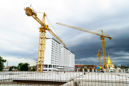 Construction site with crane near building on Cloudy storm background