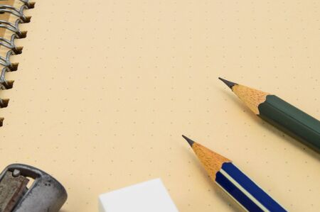 Two Wooden pencil, eraser and sharpener on recycle notebook background  photo