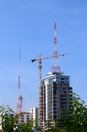 Antenna of Communication Building and modern construction crane on blue sky  photo