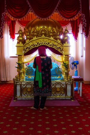A Woman Sikh pilgrims stand praying in room at Gurdwara Siri Guru Singh Sabha