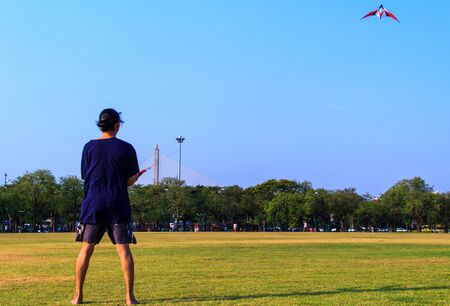 Young man flying a kite at Royal Plaza Park  Sanam Luang Park  in Bangkok