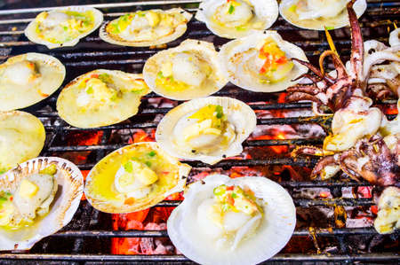 Grilled scallops topped with butter, garlic and parsley on flaming grill  Stock Photo