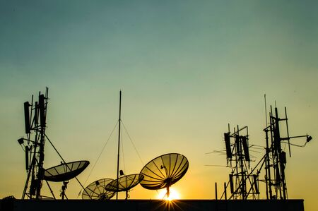 Silhouette Satellite Dish and Communication Tower on Sunset Time  Stock Photo