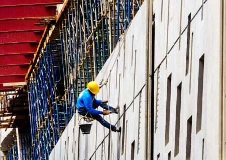 A Construction Workers high up on the wall of a new building