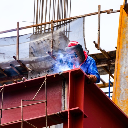 A Construction Worker welding steel bars on construction site
