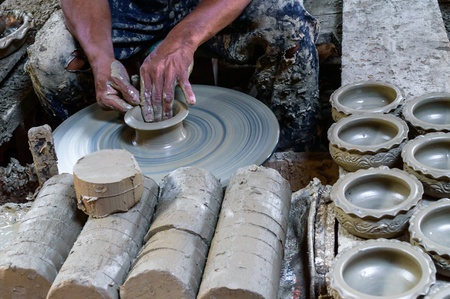 Potter makes on the pottery wheel clay pot