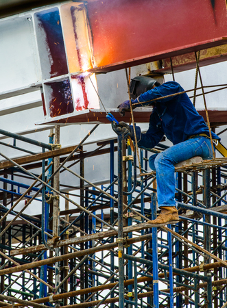 A Construction Worker welding steel bars on scaffold in construction site