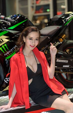 easing: BANGKOK - JUNE 24 : Unidentified model with Monster Energy Yamaha motorcycle on display at Bangkok International Auto Salon 2015 on June 24, 2015 in Bangkok, Thailand. Event of decoration and modify car. Editorial