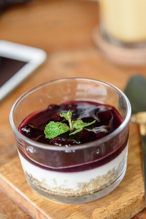 Blueberry Cheese Cake in the glass bowl on wood plate.