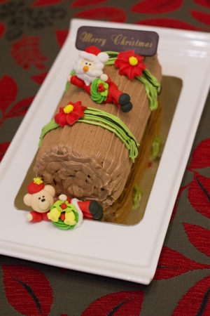 Traditional Christmas Yule Log cake decorated with santa bear and fiower mazipan  photo