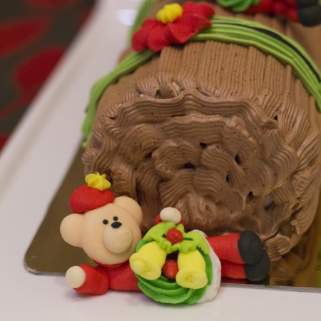 Traditional Christmas Yule Log cake decorated with santa bear and fiower mazipan
