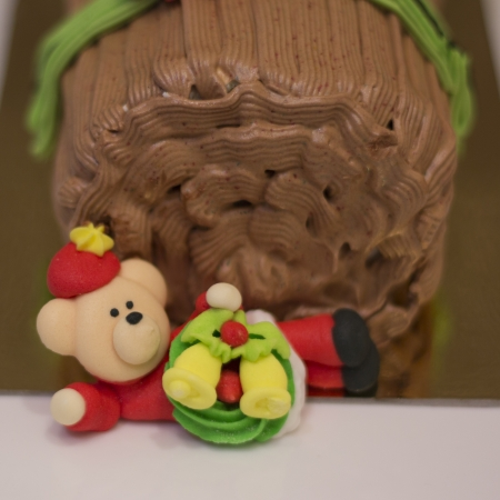 Traditional Christmas Yule Log cake decorated with santa bear and fiower mazipan.