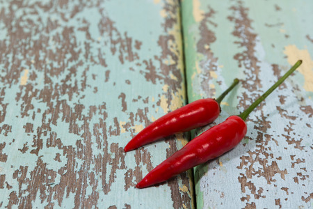 Red and green chilli on wood
