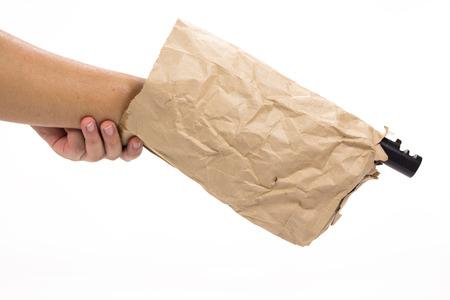 holding gun: hand holding gun in the paper bag on white background