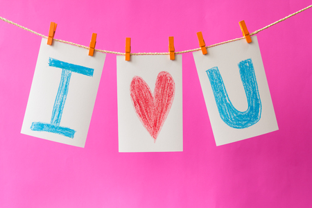 i love u: Photo cards with  hand write text I love u  and clip hanging on the clothesline on pink background