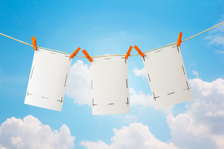 Photo cards and clip hanging on the clothesline on sky background