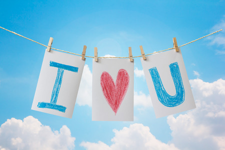 Photo cards with  hand write text I LOVE U  and clip hanging on the clothesline on sky background