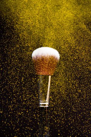 Make-up brush with yellow  powder on black background Stock Photo