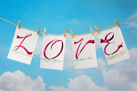 l hand: Photo cards with  hand write text  L O V E  and clip hanging on the clothesline on sky background