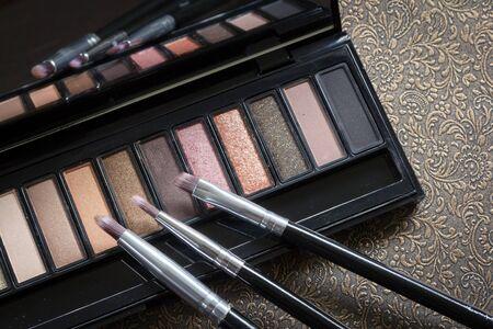 Make up brush and cosmetics on dark background