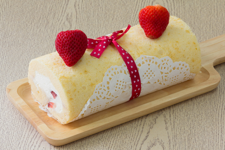 Homemade cake roll with strawberry on wooden tray
