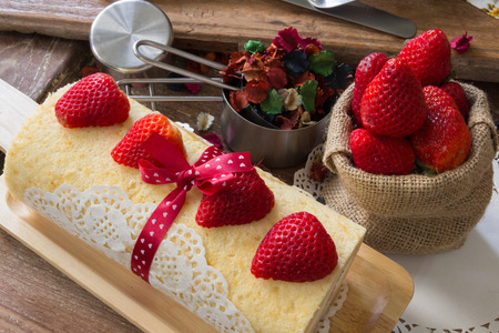 Strawberry Roll Cake on a wooden plate and strawberries in sacking bag set on with kitchen accesseries