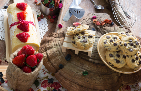 Chocolate Chip Cookies and strawberry roll on the wooden plate