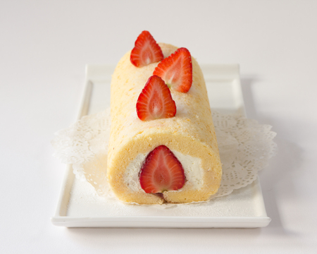 roll cake topping with strawberry on white plate