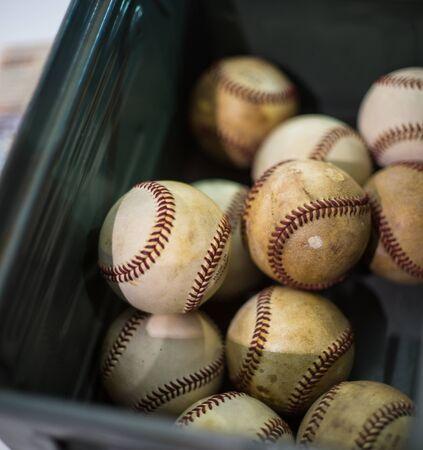 hardball: Several battered baseballs in a plastic box at flea market
