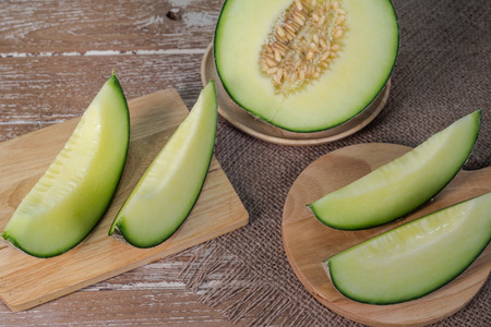 melons: Sliced of green melons on wooden plate