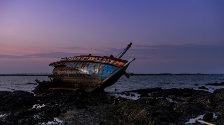 Abandoned shipwreck on the beach during sunset