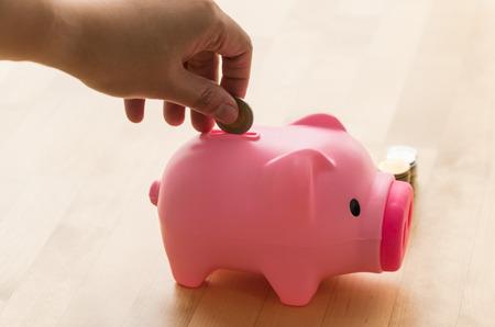 hand munt aanbrengend een spaarvarken. geld concept te redden Stockfoto