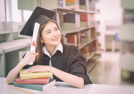 The graduated student is thinking about her future in the library of the University