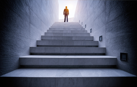 Businessman standing on top of concrete stairs with sun light Stock Photo
