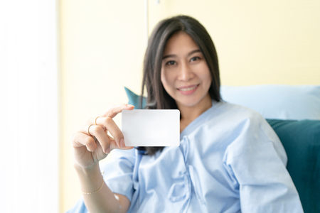 Smiling female patient on bed showing blank cradit card. Stockfoto