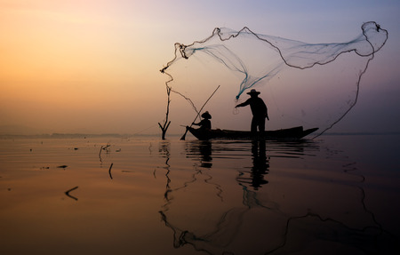 Fisher man on boat thorwing fish net to catch fish in the lake, Thailand.