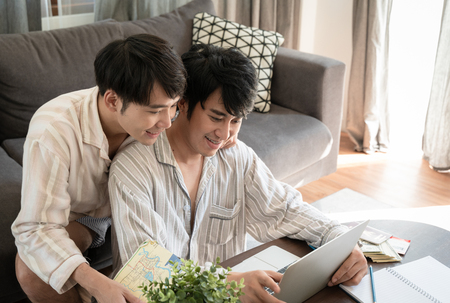 Gay couple use internet for searching  information to travel in next holiday. 版權商用圖片