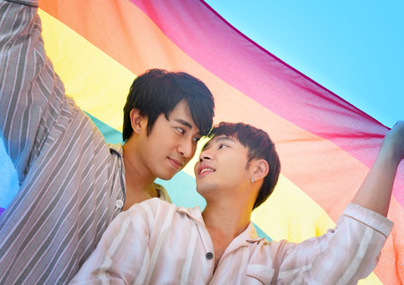 Gay couple sweet and romantic moment under rainbow flag or LGBT flag.