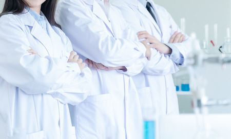 Team of professional scientists standing and crossing arms in laboratory. 免版税图像