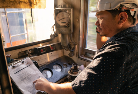 Train driver checking engine of train and gesture the hand to already from the station 免版税图像