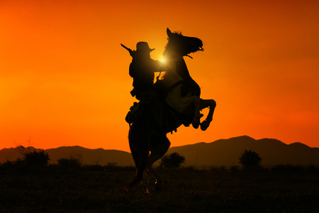 Silhouette cowboy holding short gun and riding a horse on sunrise